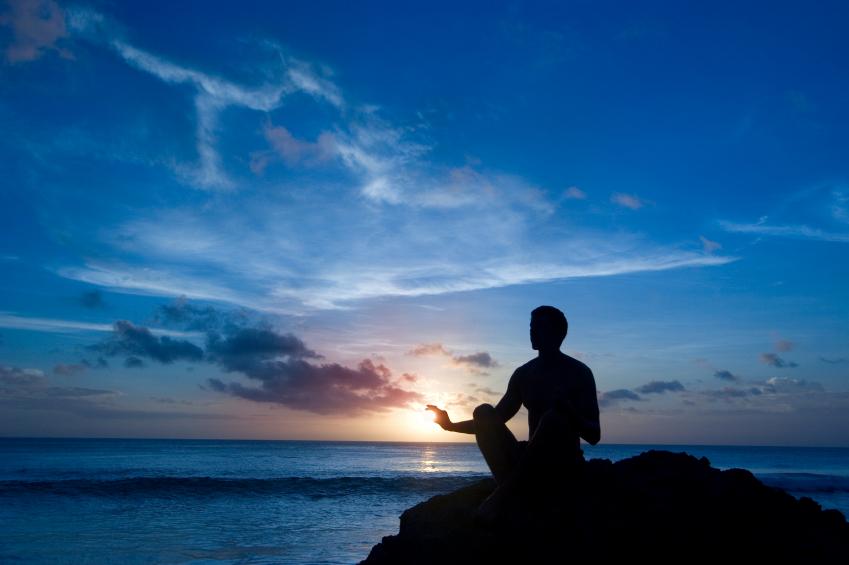 man meditating by ocean sunset